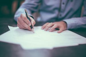 hombre firmando un contrato en Templo Consulting