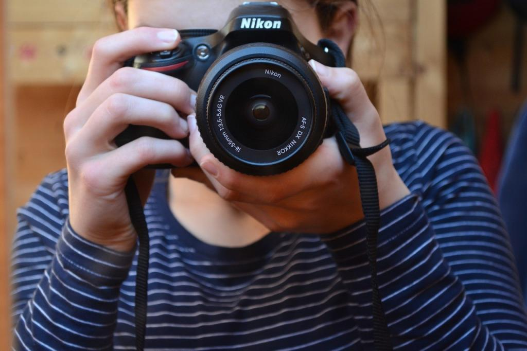 mujer con camiseta de rayas y cámara nikon reflex haciendo fotos en interior
